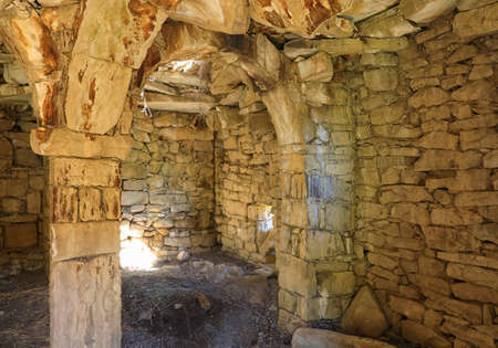 The interior of the dwelling with pillars supporting ceiling in historical abandoned village of Gamsutl located on a remote mountain peak in the Republic of Dagestan, Russia Zdjęcie Seryjne