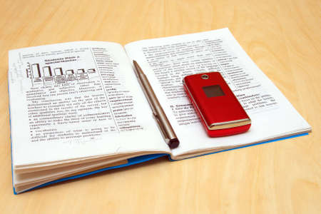proceedings: mobile phone, book and pen on table