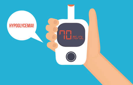 Hand with glucose meter shows low blood glucose level. Hypoglycemia concept.
