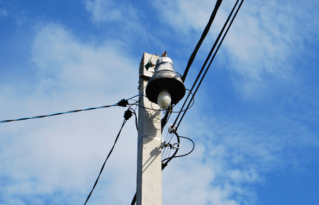 Old street lamp on an electric pole against a blue sky Stock Photo