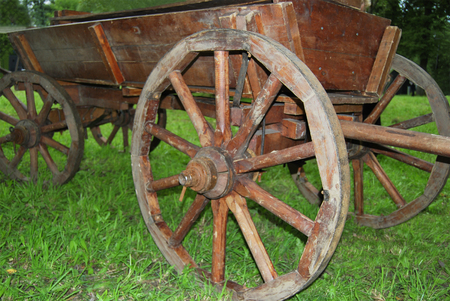 An old wooden cart on horse-drawn carriage stands on the grass.