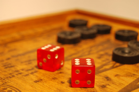The old oriental game - backgammon, two red dice, black chips. Stock Photo