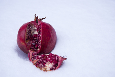 The pomegranate is red, ripe, lying on the snow. Separate lobe. Stock Photo