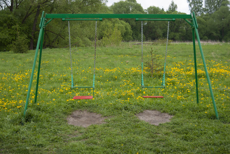 Swing for children, empty, against a background of bright green grass with yellow dandelions  Stock Photo