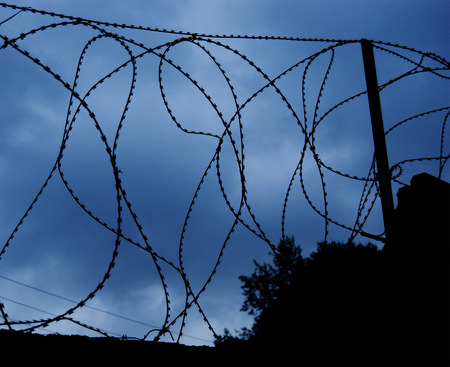 Barbed wire at the top of the fence against the backdrop of the dramatic sky. Restricted area Imagens