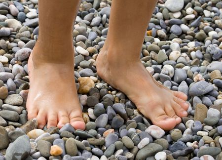 boy feet: Childish legs on pebble