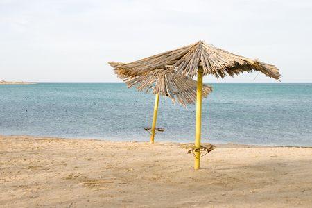 rickety: Deserted beach with old rickety sunshades