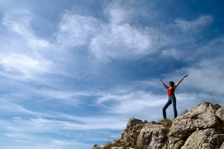 A young girl stands on the edge of a cliff with a beautiful sky with clouds photo
