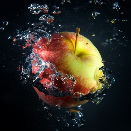 Apple is under water in a stream of air bubbles on a black background