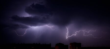 Bright branched lightning over the rooftops of urban buildings photo