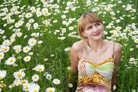 Young girl sitting on green grass with daisies photo