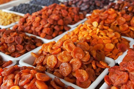 Dried fruits. Different kinds of dried apricot arranged on trays photo