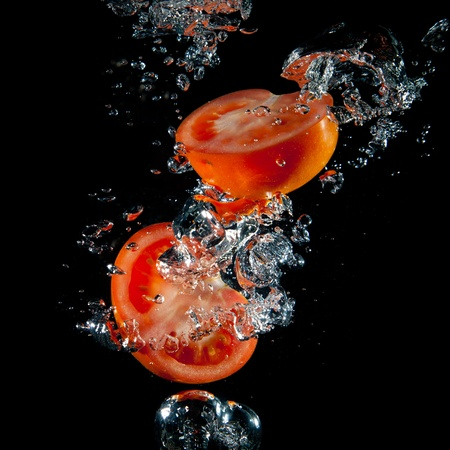 Sliced tomatoes in the water with air bubbles on a black background 版權商用圖片