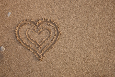 Heart drawn in the sand. Can be used as background photo