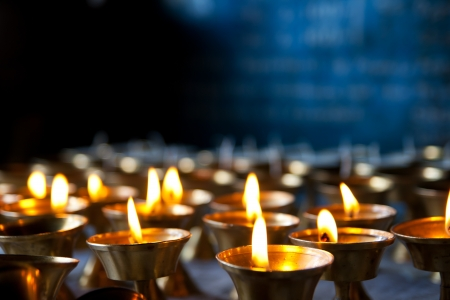 Burning candles in sconces on black blue background photo