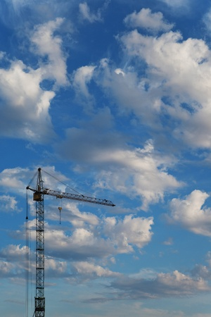 Construction crane on a background of beautiful blue sky with clouds photo