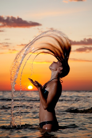 A young girl in the sea with a beautiful splashes of water from the hair at sunset photo