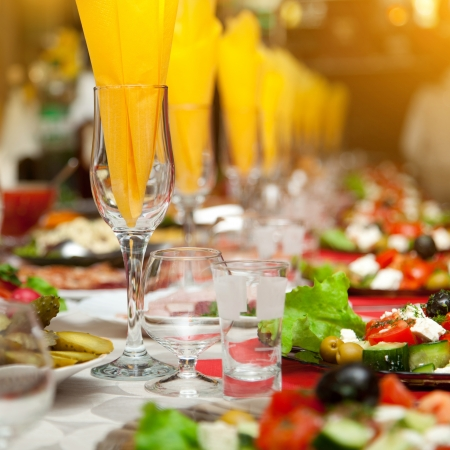catering service: Served for a banquet table. Wine glasses with napkins, glasses and salads. Stock Photo