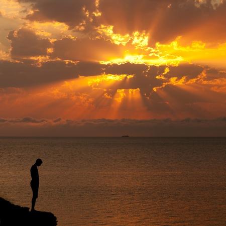 Silhouette eines Mannes auf einem Felsen über dem Meer bei Sonnenuntergang