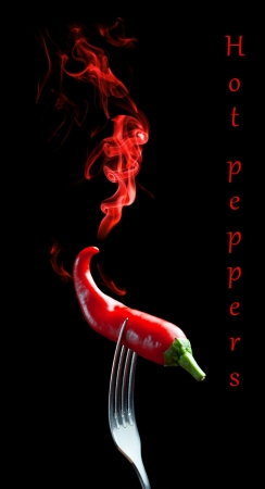 black pepper: Red hot pepper on a fork with smoke on black background