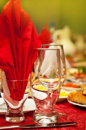 Serviert für eine Festtafel. Weingläser mit Servietten, Gläser und Salate. Standard-Bild