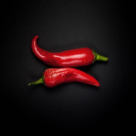 pepe nero: Due cialde di pepe rosso su sfondo nero Archivio Fotografico