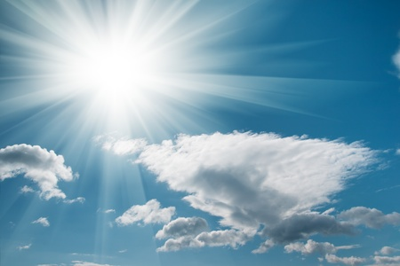 The bright sun with rays against a blue sky and floating clouds photo