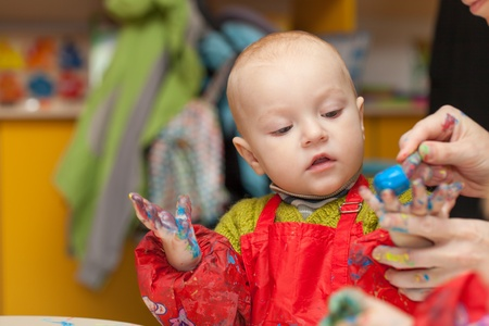 A child learns to paint finger paints 版權商用圖片