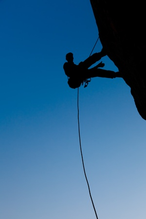 Climber on the rock against the blue sky photo