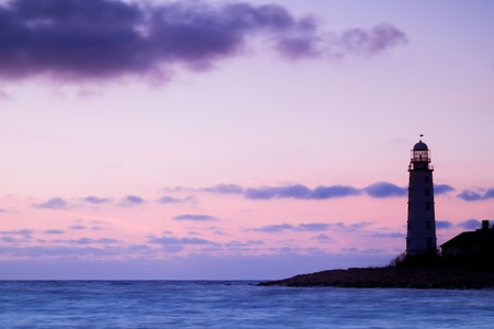 Seascape at sunset and the lighthouse on the coast 版權商用圖片