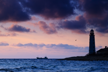 Seascape at sunset  Lighthouse on the coast and the ship at sea photo