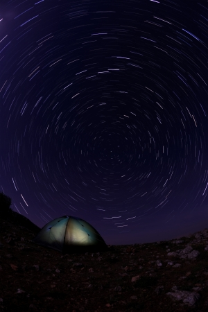 Tourist tent in the night sky with moving stars photo