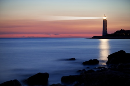 beacons: Seascape at sunset. Lighthouse on the coast Stock Photo