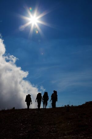 Silhouettes of tourists on against a blue sky with sun and clouds