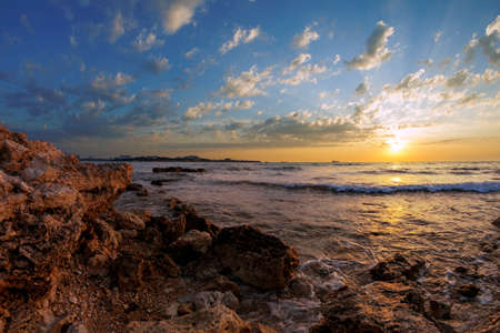 Seascape. The coastline with stones in the water at sunset Stock Photo - 17560669