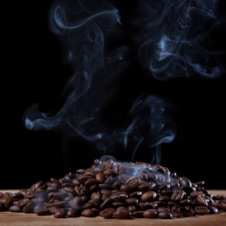 Roasted coffee with smoke on black background Stock Photo - 17552982
