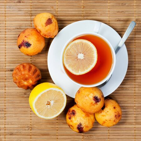 A cup of tea, cakes and lemon on a wooden napkin photo