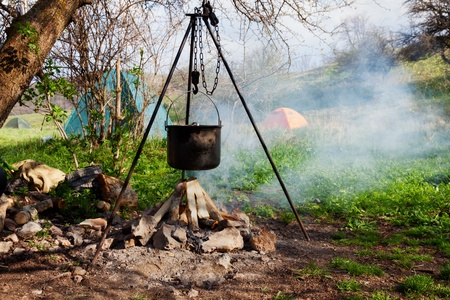 Saucepan hanging over the fire on a tripod Stock Photo - 20708411