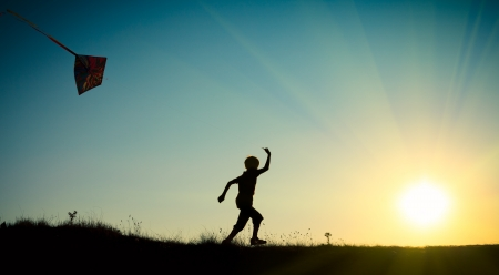 papalote: Un niño que corre con una cometa contra el cielo azul con el sol
