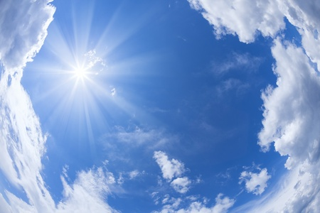 The bright sun with rays against a blue sky and floating clouds  Imagens
