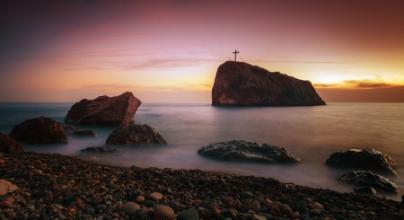Seascape. Seacoast at sunset and a cross on a rock