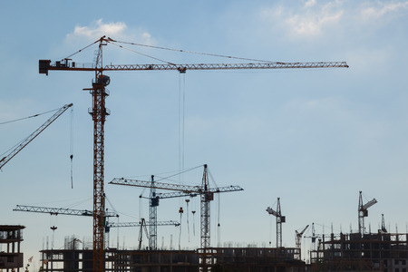 crane tower: Silhouettes of construction cranes in the sky