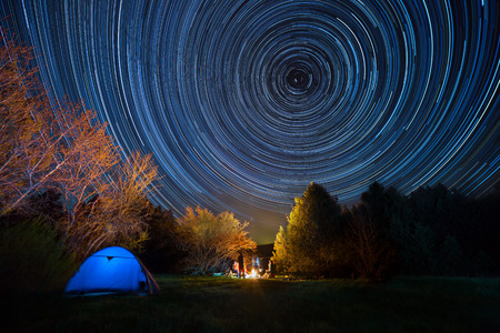 Tourist tent against the night sky with tracks from stars 版權商用圖片