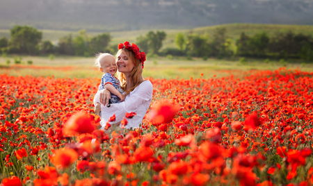 Woman with baby on hands in a field of red poppies photo