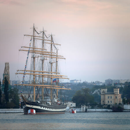 Large sailing ship in the bay prepares for mooring to the shore photo