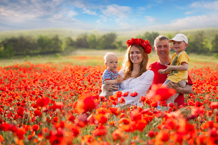 Family with children in the field of red poppies photo