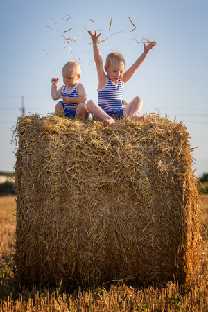 Small children play sitting on a haystack photo
