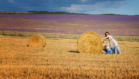 Mother with children play on the field with hay photo