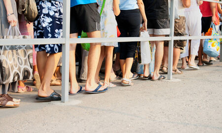 Legs of people standing in line one after another