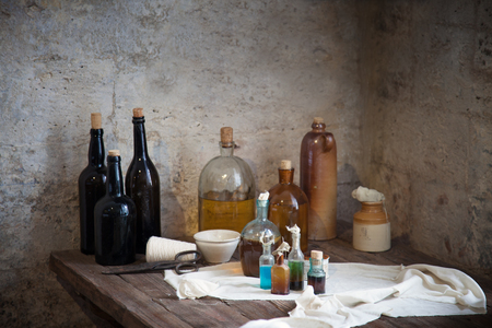 The old pharmacist's bottle with liquids on the shelf against the dilapidated walls